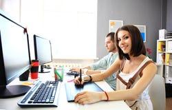 Giovane progettista femminile che per mezzo della tavola dei grafici mentre lavorando Fotografia Stock