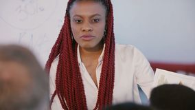 Giovane progettista femminile nero casuale felice di sviluppo che presenta progetto di costruzione ai partner in ufficio leggero  video d archivio