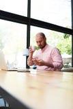 Giovane programmatore bello che si siede in caffè e che parla sul telefono Immagine Stock Libera da Diritti