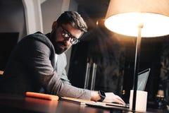 Giovane project manager che considera blocco note di carta e che scrive testo a macchina sul computer portatile contemporaneo Immagini Stock Libere da Diritti