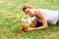 Giovane proprietario attraente del cane che mette su erba con il suo animale domestico fotografie stock