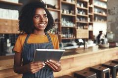 Giovane proprietario femminile che tiene compressa digitale in suo caffè che guarda aw fotografie stock