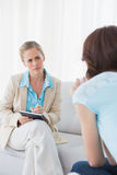 Giovane psicologo attentamente che ascolta il suo paziente fotografia stock