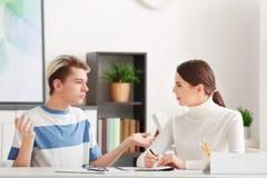Giovane psicologo femminile che lavora con il ragazzo dell'adolescente in ufficio immagini stock