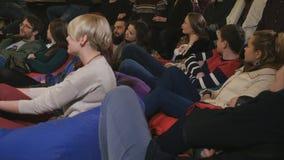 Giovane pubblico che guarda la prestazione ed il sorriso comici video d archivio