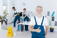 Giovane pulitore di ufficio che mostra pollice su fotografia stock