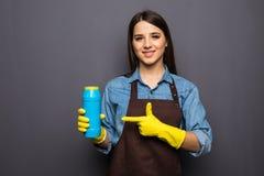Giovane pulizia della casalinga con i detersivi in mani su backgroung grigio Fotografia Stock