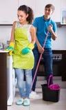 Giovane pulizia delle coppie alla cucina Fotografia Stock