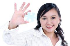 Giovane puzzle di puzzle felice della holding della donna di affari immagine stock