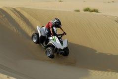 Giovane quadrato del ragazzo che biking nelle dune Fotografia Stock