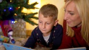 Giovane racconto della lettura della madre al bambino sotto l'albero del nuovo anno video d archivio