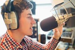 Giovane radiodiffusione radiofonica ospite nello studio Fotografie Stock Libere da Diritti