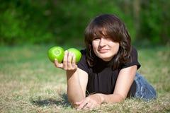 Giovane ragazza adulta che giudica due mele disponibile Immagine Stock