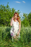 Giovane ragazza affascinante nelle prendisole bianche belle, camminata sexy nel campo fra le spighette del grano con i papaveri r Fotografia Stock Libera da Diritti