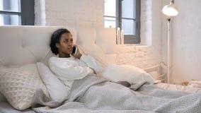 Giovane ragazza africana che parla sul telefono mentre rilassandosi a letto archivi video