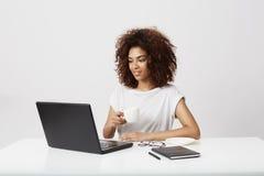 Giovane ragazza africana che tiene tazza che esamina computer portatile che sorride sopra il fondo bianco Immagini Stock Libere da Diritti