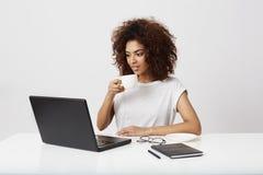 Giovane ragazza africana che tiene tazza che esamina computer portatile che sorride sopra il fondo bianco Fotografia Stock Libera da Diritti