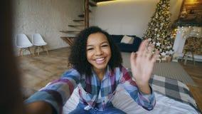 Giovane ragazza afroamericana che chiacchiera conversazione online facendo uso della macchina fotografica dello smartphone a casa Fotografia Stock
