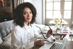 Giovane ragazza afroamericana che lavora al computer portatile in ristorante Signora graziosa con capelli ricci scuri che si sied Fotografia Stock Libera da Diritti