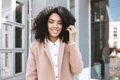 Giovane ragazza afroamericana con capelli ricci scuri che stanno signora sorridente della camicia bianca e del cappotto beige in  Fotografia Stock