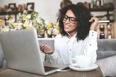 Giovane ragazza afroamericana in vetri che si siedono nel ristorante con il computer portatile Ragazza graziosa con le cuffie all Fotografia Stock Libera da Diritti