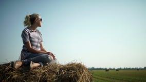 Giovane ragazza alla moda in una maglietta a strisce che si siede su un mucchio di fieno fotografia stock libera da diritti