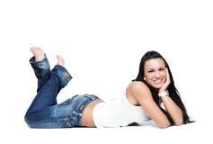 Giovane ragazza allegra in blue jeans che si trovano giù Immagine Stock