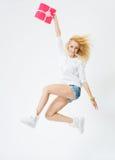 Giovane, ragazza allegra che salta con un regalo in mani, su w immagini stock libere da diritti