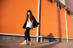 Giovane ragazza allegra con un cappuccio e un manto nero contro lo sfondo di una parete arancio fotografia stock