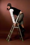 Giovane ragazza alta in protezione che si arrampica sull'alta scaletta Immagine Stock