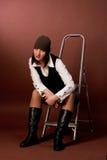 Giovane ragazza alta in protezione che si siede sulla scaletta con la testa Immagini Stock Libere da Diritti