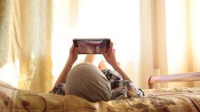 Giovane ragazza araba con il computer del pc della compressa sulla camera da letto del letto a casa donna riflessa in schermo Con video d archivio