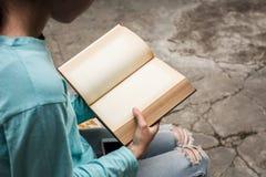 Giovane ragazza asiatica che legge un libro all'aperto a casa con crac confuso Fotografie Stock Libere da Diritti