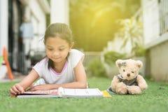 Giovane ragazza asiatica che legge un libro che si trova sul suo prato inglese della casa fotografie stock libere da diritti