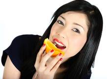 Giovane ragazza asiatica che mangia arancio fotografia stock
