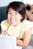 Giovane ragazza asiatica che passa in rassegna la rete sullo strato Immagine Stock