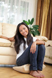 Giovane ragazza asiatica che si siede sul pavimento Immagini Stock