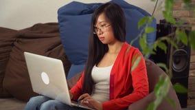 Giovane ragazza asiatica del ritratto che esamina con il sorriso la macchina fotografica e che chiacchiera online stock footage