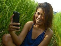 Giovane ragazza asiatica dell'isolano felice ed esotico dall'Indonesia che prende la foto dell'autoritratto del selfie con sorrid fotografia stock libera da diritti