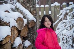 Giovane ragazza asiatica nella condizione rosa del cappotto accanto al mucchio del ceppo fotografia stock libera da diritti