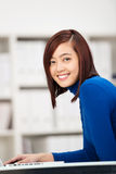 Giovane ragazza asiatica sorridente che per mezzo di un computer portatile Fotografie Stock