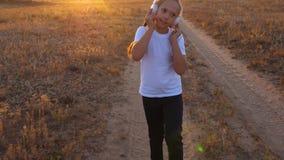 Giovane ragazza atletica in cuffie che fanno pareggiare, un addestramento della ragazza al tramonto ed ascoltare la musica stock footage