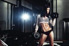 Giovane ragazza atletica di forma fisica che fa un allenamento con le teste di legno nella palestra Immagine Stock Libera da Diritti