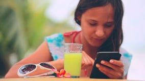 Giovane ragazza attraente che per mezzo del telefono cellulare che beve succo sano sulla spiaggia accanto agli occhiali da sole e archivi video