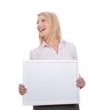 Giovane ragazza attraente che tiene la scheda di messaggio vuoto immagine stock