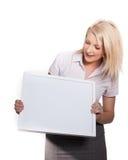 Giovane ragazza attraente che tiene la scheda di messaggio vuoto fotografie stock
