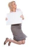 Giovane ragazza attraente che tiene la scheda di messaggio vuoto immagini stock