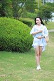 Giovane ragazza attraente cinese dello studente con capelli lunghi che posano in libro di trasporto del parco di verde della citt Immagini Stock