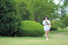Giovane ragazza attraente cinese dello studente con capelli lunghi che posano in libro di trasporto del parco di verde della citt Immagini Stock Libere da Diritti