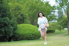 Giovane ragazza attraente cinese dello studente con capelli lunghi che posano in libro di trasporto del parco di verde della citt Fotografie Stock